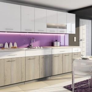Aneks kuchenny w stonowanych kolorach beżów i bieli idealnie współgra z żywą ścianą nad blatem w fiołkowym kolorze, który harmonizuje z oświetleniem nad stołem. Meble kuchenne z wysokimi szafkami górnymi zapewniają dużo miejsca na przechowywanie. Fot. Stolkar, kuchnia Luxe Blanco Dąb Truflowy.
