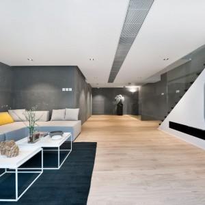 Oprócz salonu na parterze, na pierwszym piętrze znajduje się pokój rodzinny, funkcjonujący jako bardziej prywatny salon, zlokalizowany w holu kondygnacji, wpasowany delikatnie w płytką wnękę. Projekt i zdjęcia: Millimeter Interior Design.