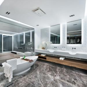 Sypialnia tworzy wspólną przestrzeń z dużą łazienką do wyłącznego użytku pani i pana domu, od której oddzielają ją jedynie szklane ścianki. Znajduje się w niej wolno stojąca wanna o nietuzinkowym kształcie i dwie umywalki. Elegancję w pomieszczeniu buduje piękna, kamienna podłoga. Projekt i zdjęcia: Millimeter Interior Design.