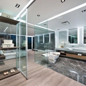 Nieopodal łazienki znalazła się również duża garderoba, również z przeszklonymi ściankami. Projekt i zdjęcia: Millimeter Interior Design.