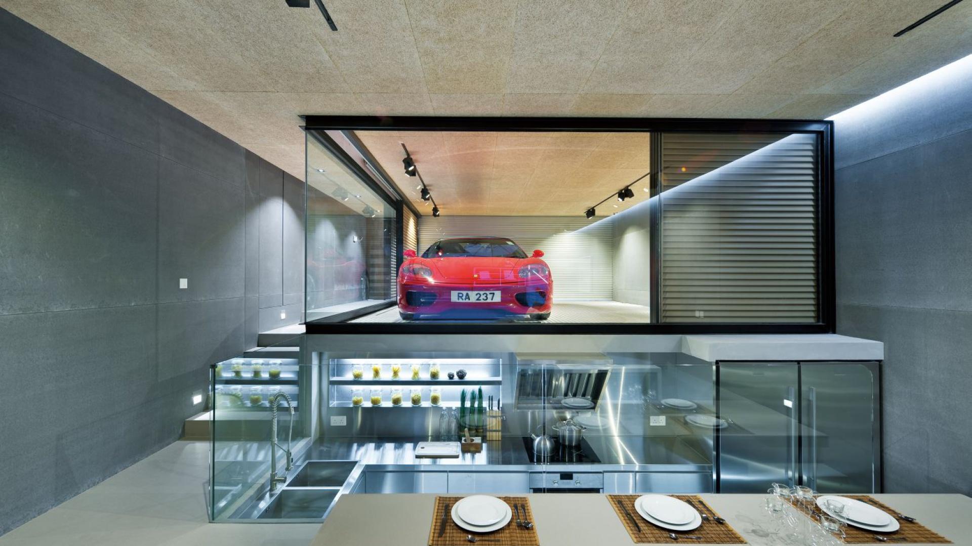 Otwarta kuchnia została tak zaplanowana, że otwiera się zarówno na parter, jak i niższą kondygnację. Wpasowana we wnękę, odgrodzoną estetycznie szklanymi ściankami, zlokalizowaną pod podestem, na którym zaplanowano dwustanowiskowy garaż. Projekt i zdjęcia: Millimeter Interior Design.