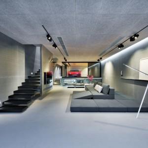 Parter budynku zajmuje przestronna strefa dzienna z nowoczesnym salonem, który sąsiaduje bezpośrednio z... przeszklonym garażem. Projekt i zdjęcia: Millimeter Interior Design.