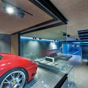 Czerwone Ferrari ustawione w przeszklonym garażu, wpasowanym we wnętrze, przy wejściu do domu, pełni niemal pełnoprawną rolę domu dekoracyjnego. Projekt i zdjęcia: Millimeter Interior Design.