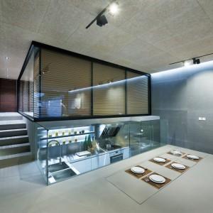 Sąsiadujący z ukrytą kuchnią stół dla sześciu osób można podnosić lub licować z podłogą w w ramach potrzeb. Projekt i zdjęcia: Millimeter Interior Design.