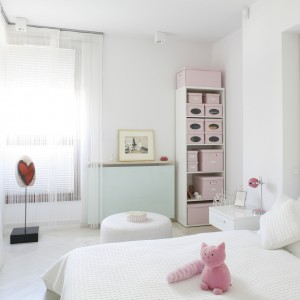 Białą sypialnię w stylu glamour ożywiono dodatkami w kolorze pastelowego różu, przez co zyskała ona subtelny, dziewczęcy wygląd. O kobiecym charakterze wnętrza świadczy również duże lustro w minimalistycznej ramie. Projekt: Piotr Gierałtowski. Fot. Bartosz Jarosz.