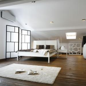 Przestrzeń na poddaszu to idealne miejsce by urządzić sypialnię. Połączenie chłodnej bieli z ciemnym drewnem pozwoliło uzyskać aurę idealną do relaksu i wypoczynku. Lekkości dodają ażurowe detale. Projekt: Konrad Grodziński. Fot. Bartosz Jarosz.