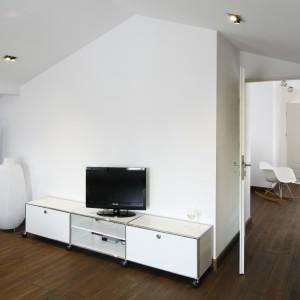 Rozrywkę zapewni telewizor ustawiony na minimalistycznej, białej szafce, zlokalizowanej tuż przy drzwiach. Z sypialnią sąsiaduje łazienka. Projekt: Konrad Grodziński. Fot. Bartosz Jarosz.