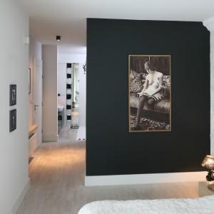 Czarna ściana z obrazem w stylu retro efektownie przełamuje wnętrze zdominowane bielą. Ten mocny detal wprowadza do wnętrza nutę artyzmu. Projekt: Monika Włodarczyk, Jarosław Jończyk. Fot. Bartosz Jarosz.