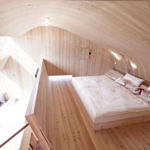 ...i pod zaokrągleniami. Sufit domku jest bowiem wyprofilowany w delikatne półkole, co ciekawie kontrastuje z mocnymi liniami i kątami okien. Projekt: Architekturbüro Jungmann&Aberjung Design Agency. Fot. DI Lukas Jungmann/Familie Pitterl.