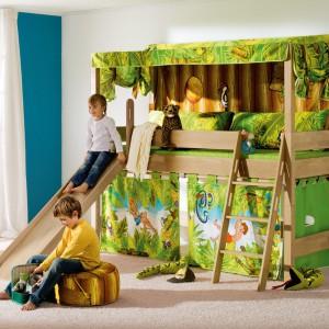 Łóżko na antresoli marki Paidi dzięki materiałowym dodatkom przypomina domek w dżungli. Radosnej zabawie sprzyja też niewielka zjeżdżalnia, dzięki której dziecko szybko wstaje z łóżka. Fot. Paidi.