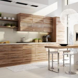 Fronty mebli kuchennych zdobi drewniany dekor w poziomie oraz mleczne subtelne przeszklenia w pasie szafek górnych, które dodatkowo zdobią podświetlenia ledowe, funkcjonujące również jako oświetlenie blatu. Kolorem zabudowa harmonizuje ze stołem jadalnianym, wspartym o ciekawą ściankę/słupek. Fot. Stolkar, kuchnia Brzoza.