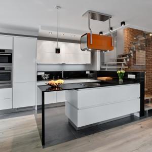 W tym nowoczesnym wnętrzu zastosowano ciekawe rozwiązanie aranżacyjne. Cegła nie jest na ścianie  w kuchni, ale wygląda jakby na niej była. Wykończono nią ścianę w przestrzeni klatki schodowej, ale ta jest otwarta na wspólną strefę dzienną, sąsiaduje bezpośrednio z kuchnią i została jedynie przeszklona od strony kuchni. Fot. Atlas Kuchnie, model Oktawia Listwowy.
