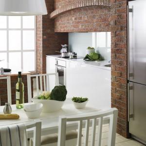 Płytki klinkierowe są idealne nie tylko na elewacje budynków. To również jedno z możliwych rozwiązań, jeśli chcemy sprawić sobie ceglaną ścianę w kuchni. Tutaj, wspólnie ze stylizowanymi meblami w jadalni tworzą delikatnie rustykalną aranżację. Fot. Roeben.