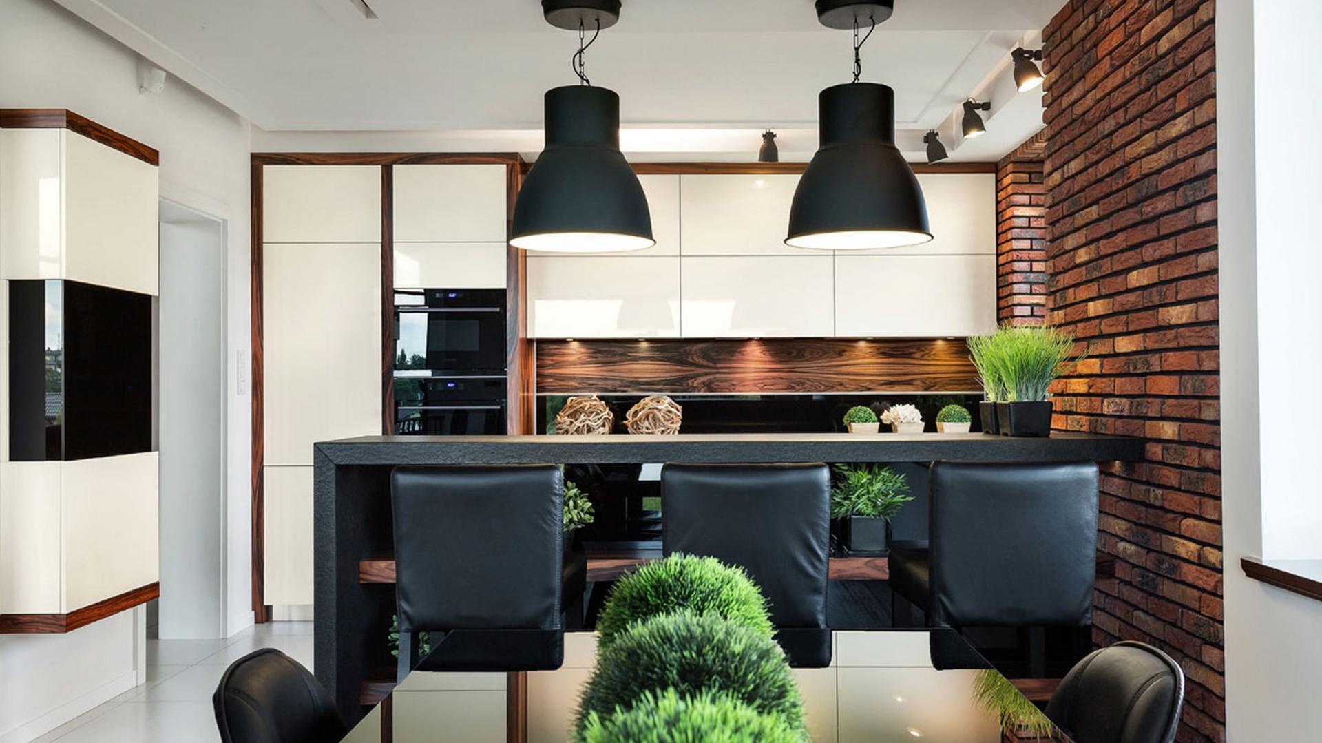 Aranżacja tej kuchni zyskała nazwę Brick - od cegły, którą pokryto ściany. Głęboka, czerwona barwa ociepla aranżację, opartą o białą zabudowę w chłodnym połysku. Z kolei czarne loftowe lampy i minimalistyczna stylistyka mebli sprawiają, że wnętrze nabiera loftowego charakteru. Fot. Pracownia Mebli Vigo.