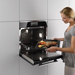 Prowadnice ułatwiają wyjmowanie oraz wkładanie dań, gdy piekarnik jest zainstalowany w wysokiej zabudowie. Nowoczesne modele mają także chłodne drzwiczki w trakcie pieczenia i blokady uruchomienia, np. przed dziećmi. Na zdjęciu: piekarnik H 6860 BP firmy Miele. Fot. Miele.