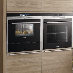 Przykład modnej, a zarazem praktycznej zabudowy: piekarnik, obok urządzenie do gotowania na parze, a pod nim szuflada do podgrzewania naczyń i dań. Gotowe dania można stawiać na blacie obok. Na zdjęciu: piekarnik HB36D575 marki Siemens. Fot. Siemens.
