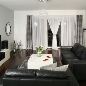 Otwarty na kuchnię salon został urządzony w stonowanych czarno-białych kolorach. Szara ściana za telewizorem stanowi ciekawy akcent stylistyczny. Projekt: Magdalena Biały. Fot. Bartosz Jarosz.