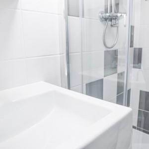Strefę prysznica zaznaczono odmiennymi płytkami na ścianie. Czarne i białe kwadraty nawiązują do uniwersalnego motywu szachownicy. Projekt i zdjęcia: Ewelina Golinowska, EG Projekt.