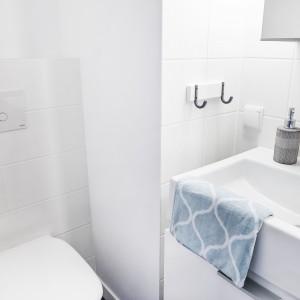 Przestrzeń niewielkiej łazienki optycznie powiększa śnieżna biel: białe są płytki, umywalka i wc. Projekt i zdjęcia: Ewelina Golinowska, EG Projekt.