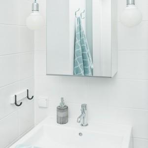 W łazience, zdominowanej przez śnieżną biel i delikatne szarości, barwnym akcentem są dodatki oraz turkusowe oploty, na których zawisły edisonowskie żarówki. Projekt i zdjęcia: Ewelina Golinowska, EG Projekt.