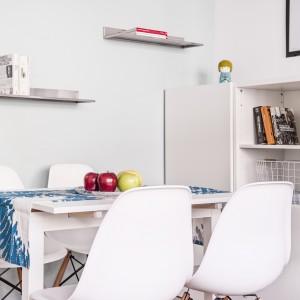 W bardzo małą przestrzeń udało się wpasować również niewielką jadalnię. Małemu rozkładanemu stołowi w białym kolorze towarzyszą eamesowskie krzesła. Projekt i zdjęcia: Ewelina Golinowska, EG Projekt.