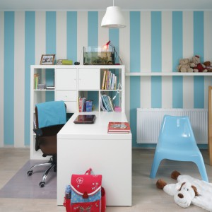 W tym pokoju przestrzeń zorganizowano tak, aby dziecko miało wygodne miejsce do nauki, jak i do zabawy. Charakter nadała wnętrzu tapeta w niebieskie pasy, do które dobrano białe meble oraz jasną, drewnianą podłogę. Projekt: Beata Ignasiak. Fot. Bartosz Jarosz.