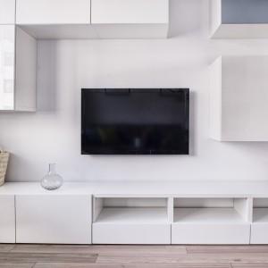 Zabudowę przy TV wykonano w takim samym kolorze, jak meble kuchenne. Taka optyczna kontynuacja przestrzeni kuchni spaja wizualnie dwa wnętrza i powiększa optycznie całe mieszkanie. Projekt i zdjęcia: Ewelina Golinowska, EG Projekt.