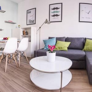 Funkcje w mieszkaniu urządzono w prostym rzędzie. Przy samym drzwiach znalazła się kuchnia, pełniąca również funkcję przedpokoju, na jej granicy z salonem urządzono jadalnię, a salon wpasowano w miejsce sąsiadujące z dużym oknem. Projekt i zdjęcia: Ewelina Golinowska, EG Projekt.
