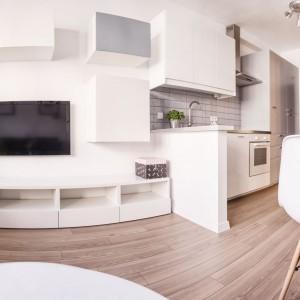Białe meble, jasne ściany, brak zasłon w oknach, podłoga w kolorze drewna i płytki, imitujące tradycyjne kafle nad blatem. Te wszystkie elementy budują we wnętrzu skandynawski klimat. Projekt i zdjęcia: Ewelina Golinowska, EG Projekt.