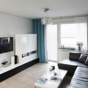 Niewielki salon urządzono w uniwersalnej palcie kolorów. Dominuje tu biel i czerń, całość ożywia turkus. Projekt: Marta Kilan. Fot. Bartosz Jarosz.