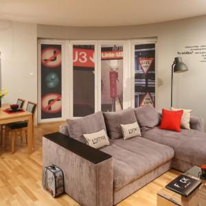 W urządzonym w stylu loft mieszkaniu obszerny narożnik w szarym kolorze organizuje strefę wypoczynkową, oddzielając ją tym samym od kuchni i jadalni. Projekt: Iza Szewc. Fot. Bartosz Jarosz.