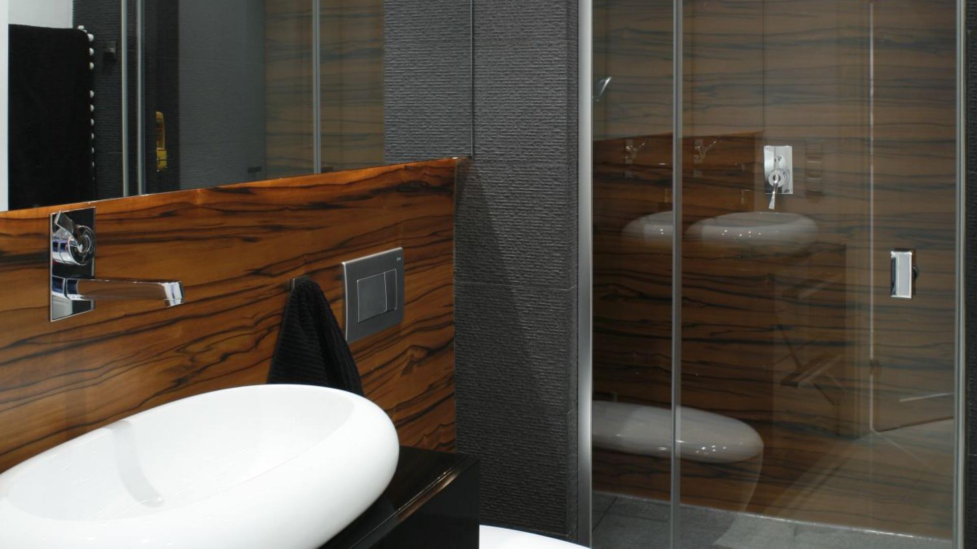 Ciemne, grafitowe płytki zestawiono z ciemnym drewnem o wyraźnym rysunku, dzięki czemu łazienka jest bardzo elegancka i stylowa. Projekt: Monika i Adam Bronikowscy. Fot. Bartosz Jarosz.