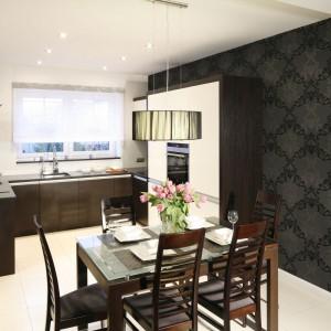 Przestrzeń tej eleganckiej kuchni i jadalni spaja ściana wykończona wzorzystą tapetą. Jadalnia to stół dla 4-6 osób, korespondujący materiałem i kolorem z meblami kuchennymi. Projekt: Magdalena Wielgus-Biały. Fot. Bartosz Jarosz.
