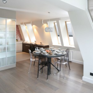 Okrągły stół jadalniany pełni rolę mebla, zamykającego przestrzeń kuchni. Towarzyszą mu kolorowe krzesła - czarne harmonizują ze stołem, przeźroczyste pozwalają osiągnąć efekt lekkości, dzięki czemu jadalnia nie przytłacza wizualnie wnętrza. Projekt: Małgorzata Borzyszkowska. Fot. Bartosz Jarosz.
