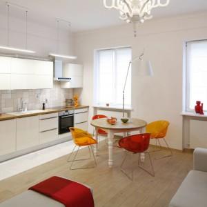W tym niewielkim mieszkanku, w którym salon połączono z jednorzędowym aneksem kuchennym, mały stół, wyznaczający granicę pomiędzy poszczególnymi funkcjami był jedynym rozwiązaniem, pozwalającym na urządzenie jadalni. Stał się on również niezwykłym elementem aranżacyjnym, a towarzyszące mu kolorowe krzesła ożywiają przestrzeń i harmonizują z barwnymi dodatkami w kuchni i salonie. Projekt: Agnieszka Żyła. Fot. Bartosz Jarosz.