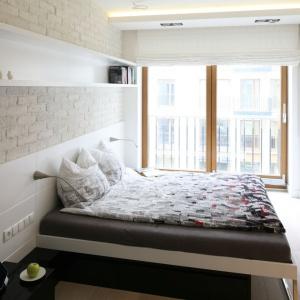 Nieduża sypialnia, która mieści w sobie wygodne łóżko wcale nie małych rozmiarów. Półki umieszczone na ścianie pozwalają na przechowywanie książek czy też płyt, ale nie zabierają przestrzeni z pokoju. Projekt: Monika i Adam Bronikowscy. Fot. Bartosz Jarosz.