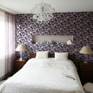 Wzorzysta tapeta za łóżkiem, uzupełniona o dekoracyjną lampę sufitową sprawia, że sypialnia jest elegancka i bardzo szykowna. Aby nie przytłaczać tego efektu w oknach zawieszono dwukolorowe firanki, tzw. makarony. Projekt: Piotr Stanisz. Fot. Bartosz Jarosz.