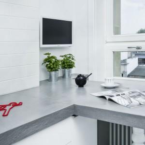 Blat kuchenny poprowadzony wzdłuż jednej ściany, zakręca przy oknie, wspierając się tam na stylizowanych, białych nogach, tworząc mini-jadalnię przy oknie. Projekt i zdjęcia: Ewelina Golinowska, EG Projekt.