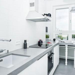 Kuchnię urządzono w kolorach bieli i chłodnych szarości. Konglomeratowy blat harmonizuje idealnie z posadzką na podłodze, wykonaną z mieszanki betonu i żywicy. Projekt i zdjęcia: Ewelina Golinowska, EG Projekt.