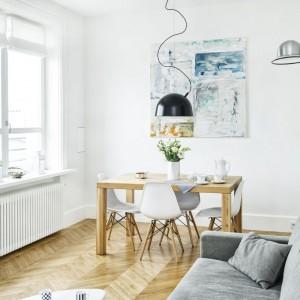 Z kolei przy przeciwległej ścianie stanął prosty, nowoczesny stół dębowy oraz autentyczne designerskie krzesła klasyki projektu Charles  ay Eames. Projekt i zdjęcia: Ewelina Golinowska, EG Projekt.