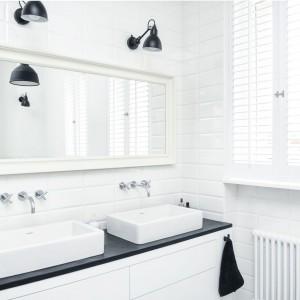 W łazience dominują czerń i biel, eksponujące się nawzajem. Białe, tradycyjne kafle wydobywają czerń z zawieszonych na ścianie technicznych kinkietów, a czarny blat wieńczący szafkę podumywalkową jest idealnym tłem dla białych, prostokątnych umywalek. Projekt i zdjęcia: Ewelina Golinowska, EG Projekt.