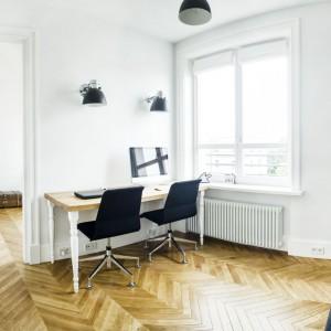 Większe, dwuosobowe biurko znalazło się w gabinecie, którego rolę pełni przestronne pomieszczenie z dużą ilością przestrzeni i światła. Oszczędny wystrój i jasne kolory uspokajają myśli pracujących domowników. Projekt i zdjęcia: Ewelina Golinowska, EG Projekt.