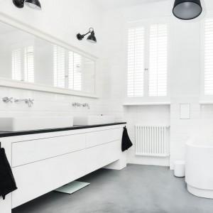Podłogę w łazience - podobnie, jak w kuchni - pokryto posadzką wylaną z mieszanki betonu i żywicy, zyskując jednorodną powierzchnię bez kłopotliwych w czyszczeniu fug. Projekt i zdjęcia: Ewelina Golinowska, EG Projekt.