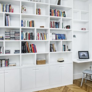 Inną ścianę w sypialni w całości pokrywa duża zabudowa z licznymi, na przemian dzielonymi na większe i mniejsze prostokąty, półkami. Projekt i zdjęcia: Ewelina Golinowska, EG Projekt.