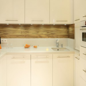 Bardzo mała kuchnia w wakacyjnym mieszkaniu wymagała urządzenia jej niemal całkowicie w bieli, aby do maksimum powiększyć jej wnętrze. Biały jest zatem również blat i podwieszana komora zlewozmywaka. Projekt: Małgorzata Galewska. Fot. Bartosz Jarosz.
