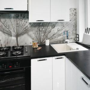 Biały jednokomorowy zlewozmywak z ociekaczem wkomponowano w róg kuchni, co pozwoliło wygospodarować więcej wolnego miejsca na blacie. Biel kontrastuje mocno z czernią i sprawia, że zlew jest bardzo widoczny. Projekt: Marta Kilan. Fot. Bartosz Jarosz.
