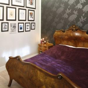 Antyczne, misternie zdobione łoże z drewna jest najmocniejszym elementem aranżacji. Ciemna tapeta z tłoczonymi wzorami jest dla niego eleganckim tłem, które nadaje wnętrzu powagi. Projekt: Monika Gorlikowska. Fot. Bartosz Jarosz.