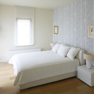Jasna sypialnia, zaaranżowana w romantycznym stylu. Białe łóżko ustawiono centralnie przy największej ścianie w sypialni, co zapewniło swobodny dostęp do niego z obu stron. Projekt: Małgorzata Borzyszkowska. Fot. Bartosz Jarosz.