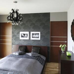Szeroki pas eleganckiej tapety pełni rolę przedłużenia wezgłowia. Pozostałą płaszczyznę ściany wykończono panelami w kolorze ciemnego drewna. Projekt: Anna Gruner. Fot. Bartosz Jarosz.