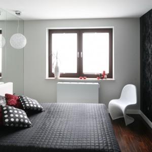Zastosowane na ścianie za łóżkiem lustra odbijają czarną tapetę z wytłoczonym wzorem inspirowanym roślinami. Projekt: Agnieszka Burzykowska-Walkosz. Fot. Bartosz Jarosz.